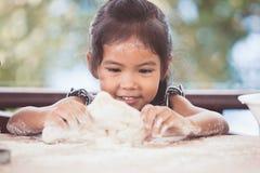 Милая азиатская девушка маленького ребенка подготавливает тесто для печь печений Стоковая Фотография RF