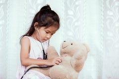 Милая азиатская девушка маленького ребенка при стетоскоп играя доктора стоковое фото