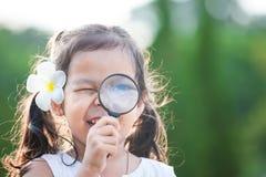 Милая азиатская девушка маленького ребенка смотря через лупу Стоковое Изображение RF