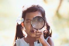 Милая азиатская девушка маленького ребенка смотря через лупу Стоковое Фото
