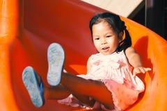 Милая азиатская девушка ребенка имея потеху для того чтобы сыграть слайдер Стоковые Изображения RF