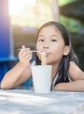 Милая азиатская девушка ребенк есть чашку лапши instand, Стоковая Фотография RF