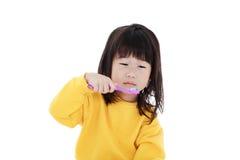Милая азиатская девушка с зубной щеткой в зубах щетки руки Китайский g Стоковые Изображения RF