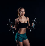 Милая атлетическая модельная девушка в sportswear с гантелями в студии против черной предпосылки Идеальная женская диаграмма спор Стоковые Фото