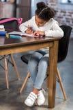 Милая Афро-американская девушка девушки сидя на таблице и делая домашнюю работу Стоковая Фотография