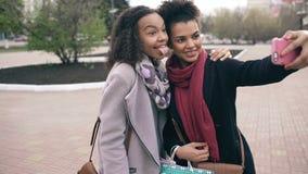 Милая Афро-американская женщина 2 принимая selfie с хозяйственными сумками и усмехаться Друзья имеют потеху после посещая продажи видеоматериал