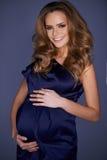 Милая беременная женщина в элегантном синем платье стоковые фотографии rf