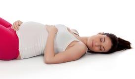 Милая беременная женщина отдыхая в ее тренировке стоковое изображение rf