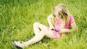 Милая белокурая девушка во времени preschool сидя в зеленой траве играя с умным телефоном акции видеоматериалы