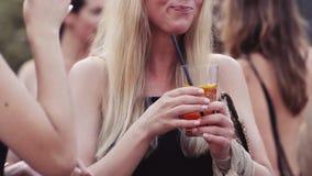 Милая белокурая девушка выпивает коктеиль с льдом во время партии бормотушк содружественная Померанцовый коктеил Закройте вверх п видеоматериал