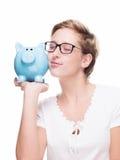 Милая белокурая женщина прижимаясь с piggybank Стоковые Изображения RF