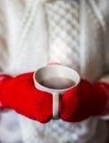 Милая белокурая маленькая девочка держа горячий испаряясь конец чашки чая вверх по фото Стоковое фото RF