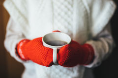 Милая белокурая маленькая девочка держа горячий испаряясь конец чашки чая вверх по фото Стоковые Изображения