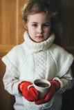 Милая белокурая маленькая девочка держа горячий испаряясь конец чашки чая вверх по фото Стоковая Фотография RF