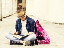 Милая белокурая школьница девушки читая книгу пока сидящ около школы Образование Стоковые Фото