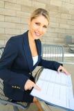Милая бизнес-леди делая вход в ее календарь Стоковые Изображения