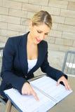 Милая бизнес-леди делая вход в ее календарь Стоковые Фотографии RF
