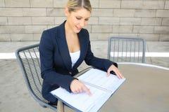 Милая бизнес-леди делая вход в ее календарь Стоковое Изображение
