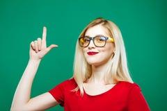 Милая блондинка показывает вверх пальцем и усмехается на зеленой предпосылке Портрет красивой девушки в студии Стоковые Фотографии RF