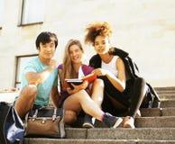 Милая группа в составе teenages на здании университета с книгами Стоковое Фото