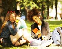 Милая группа в составе teenages на здании университета с книгами Стоковая Фотография