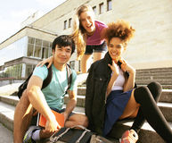 Милая группа в составе teenages на здании университета с книгами Стоковое фото RF