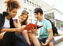 Милая группа в составе teenages на здании университета с huggings книг, назад к школе Стоковое Изображение