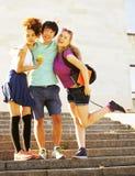 Милая группа в составе teenages на здании университета с huggings книг Стоковые Изображения
