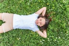 Милая девочка лежа на луге стоковые фото
