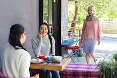 Милая девушка бежать к встречать к подругам которые уже sittin Стоковые Фото
