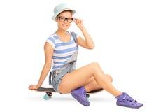 Милая девушка битника сидя на скейтборде Стоковая Фотография