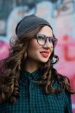 Милая девушка битника усмехается Она имеет красные губы и вьющиеся волосы Она носит стекла для визирования Стоковые Изображения RF