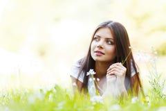 Милая девушка брюнет кладя на траву Стоковые Изображения
