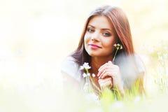 Милая девушка брюнет кладя на траву Стоковые Фото