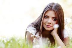 Милая девушка брюнет кладя на траву Стоковое Изображение RF