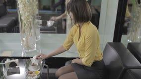 Милая девушка брюнет сидит в гостинице на софе и выпивает чай акции видеоматериалы