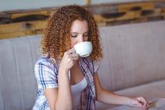 Милая девушка вьющиеся волосы наслаждаясь чашкой кофе Стоковые Фото