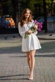 Милая девушка в белом платье и красивый букет тюльпанов. Стоковое фото RF