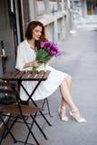 Милая девушка в белом платье и красивый букет тюльпанов. Стоковая Фотография