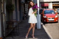 Милая девушка в белом платье и красивый букет тюльпанов. Стоковые Изображения RF
