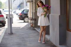Милая девушка в белом платье и красивый букет тюльпанов. Стоковое Изображение