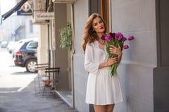 Милая девушка в белом платье и красивый букет тюльпанов. Стоковые Изображения