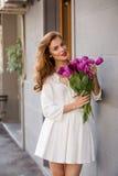 Милая девушка в белом платье и красивый букет тюльпанов. Стоковые Фотографии RF