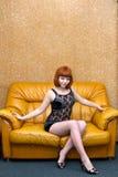 Милая девушка сидя на софе Стоковое Изображение RF