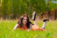 Милая девушка в оранжевом платье кладя на траву Стоковые Фото