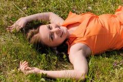 Милая девушка в оранжевом платье кладя на траву Стоковое Изображение