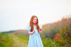 Милая девушка в поле мака цветков на открытом воздухе 2th confusedly леты девушки Стоковые Изображения RF