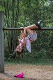 Милая девушка в платье и шорты вися вверх сторону вниз на взбираясь рамке outdoors Стоковое Изображение RF