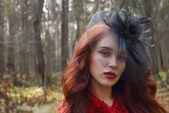 Милая девушка в черной ретро шляпе представляет в лесе Стоковая Фотография RF