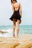Милая девушка в черном платье лета на больших камнях Стоковое фото RF